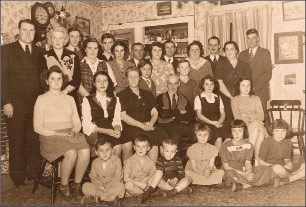 Bill Aldrich (standing, wearing v-neck sweater) and his extended family celebrate Christmas in the parlor of the Aldrich House in 1945. Note star on top of the tree in top left corner.