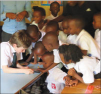 Mack Levy surrounded by new friends at school in Rwanda