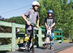 Kids on scooters enjoying the skatepark