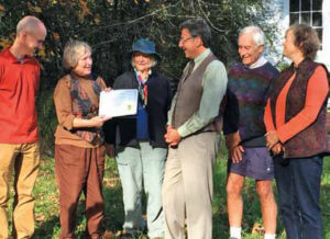 Ken Turino of Historic New England, third from right, presents the Community Preservation Grant to the Root District Game Club's Jean Lawe. Other Game Club members in the photograph, from left to right: Brian Cook, Suzie Wallis, John Lawe and Courtney Dobyns. The Lawes and Suzie Wallis first became involved with the schoolhouse in the 1960s and have been working to preserve the building ever since.